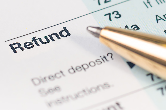 A close-up of a refund form with a pen