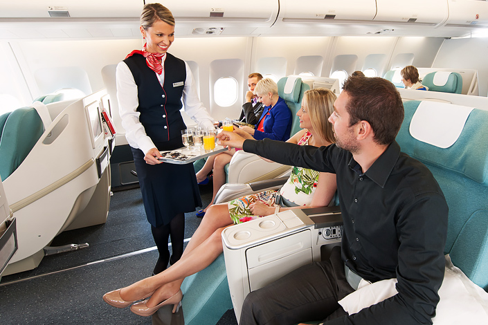 A flight attendant taking care of Business Class passengers aboard a Czech Airlines aircraft
