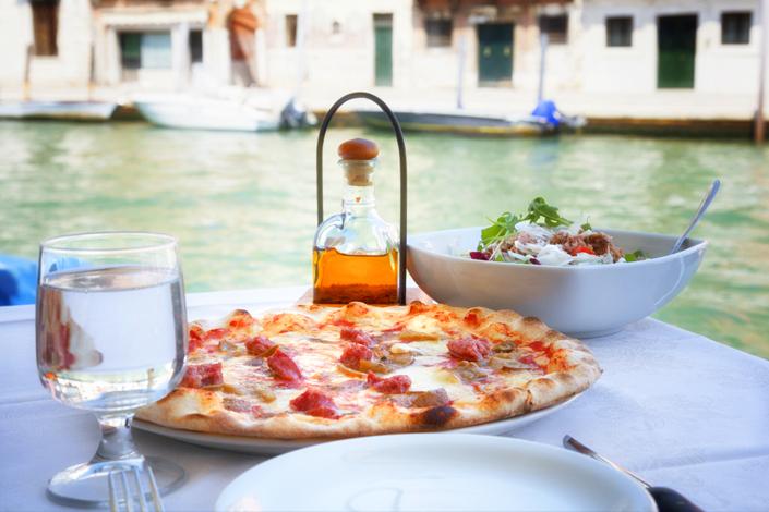 Pizza italienne traditionnelle, servie avec une salade et un verre d'eau sur la terrasse du restaurant près d'un canal vénitien