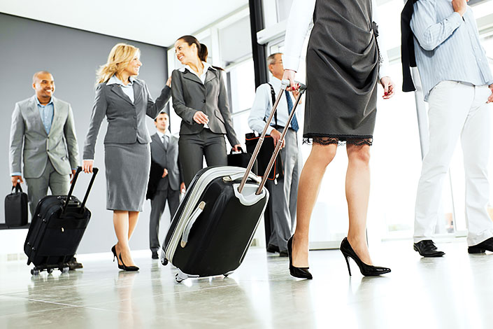 A group of men and women in business attire passing through a hall at an airport