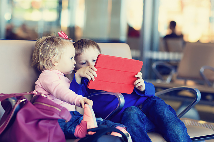 Two children sitting on a seat in an airport hall, playing online games while waiting for boarding