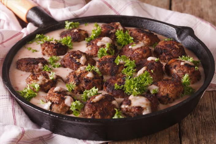 Traditionelle schwedische Fleischbällchen Köttbullar mit Soße in einer Pfanne auf einem Holztisch serviert