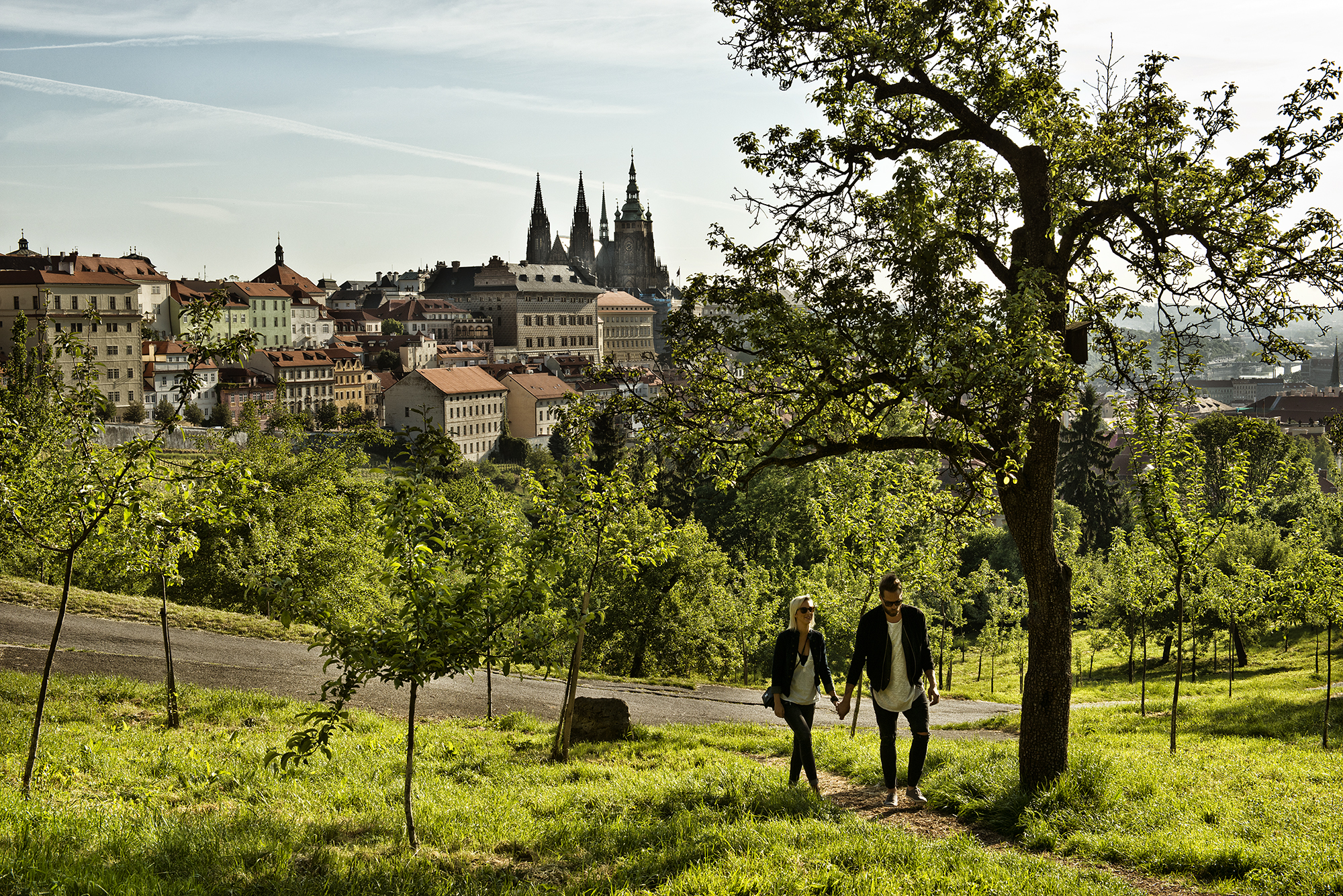 A spring view of the Prague Castle panorama in the background, with a young couple walking up the Petrín Hill path in the foreground