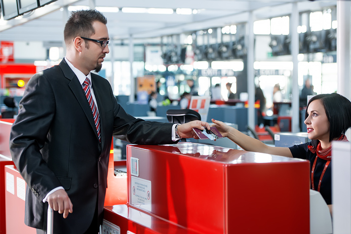 A young man in a suit with a piece of baggage is checking in at a Czech Airlines counter at Václav Havel Airport Prague