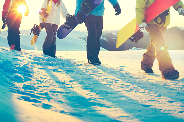 Four snowboarders walking with snowboards in hands on a snow-covered ski slope in a ski resort