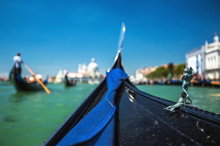 Venise - détail de la proue d'une gondole naviguant le long du canal, avec la basilique Santa Maria della Salute en arrière-plan