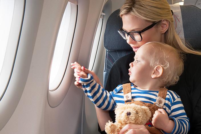A mother with a small child on her lap in a window seat aboard a Czech Airlines aircraft