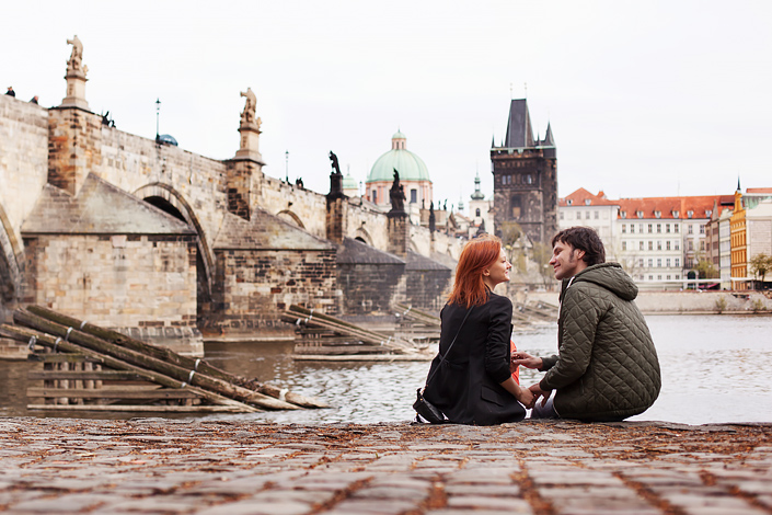 Prag - junges Paar sitzt am Moldauufer mit Aussicht auf die Karlsbrücke