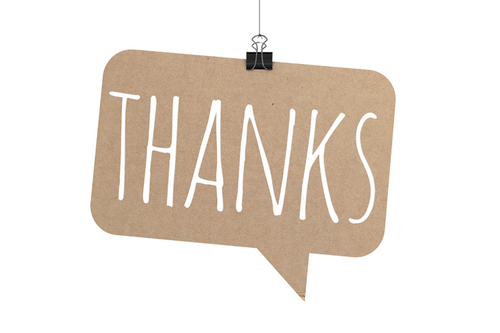 "A sign hanging on a string reading ""Thanks"""