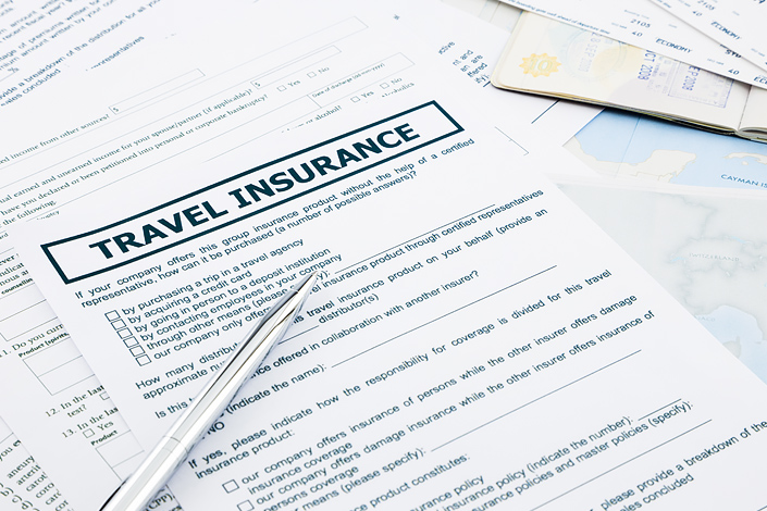 A travel insurance form with a pen
