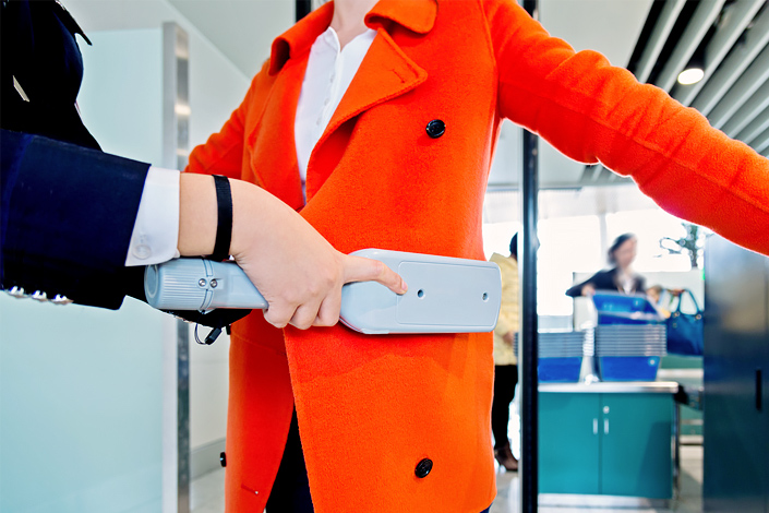Security check at the airport - a woman is subjected to a manual metal detector search