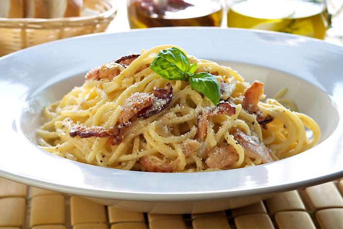 Un plato italiano tradicional de espagueti Carbonara, servido en un plato de cerámica blanca