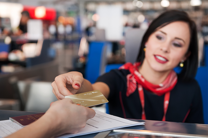 Czech Airlines check-in desk assistant accepting travel documents and an OK Plus Gold Membership Card from a passenger