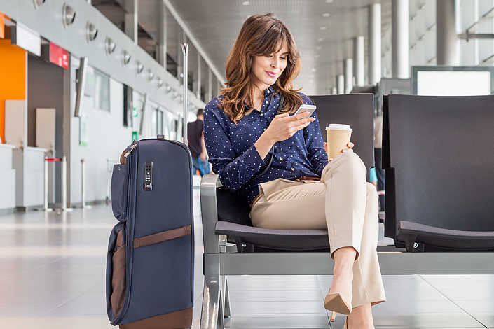A young woman using a mobile phone sitting next to her baggage in an airport hall, waiting for boarding