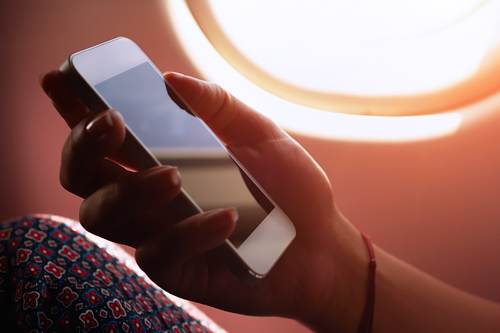 "A woman sitting in an aircraft cabin holding a mobile phone in her hand with the ""Airplane / Flight Safe"" mode activated"