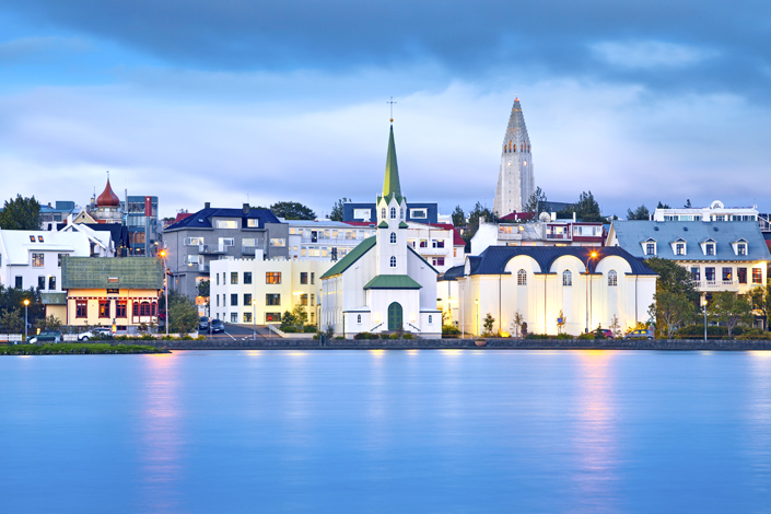 Reykjavik - a view of a traditional wooden church on the shore of a bay, with the Hallgrimskirkja church in the background